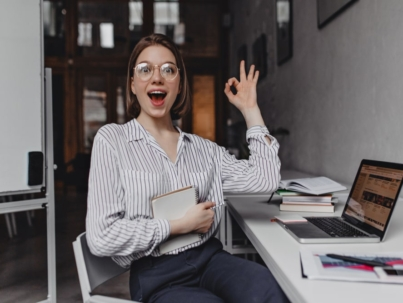 joyful-girl-office-worker-shows-ok-sign-portrait-of-woman-in-pants-and-light-blouse-at-workplace (1)-min