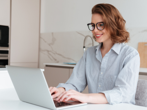 elegant-smiling-woman-in-glasses-and-striped-shirt-using-laptop-computer-while-siting-at-table-in-kitchen